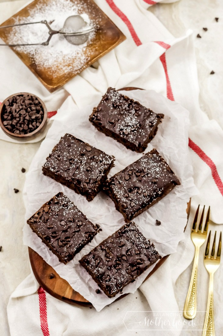 black bean brownies on counter with chocolate chips and powdered sugar