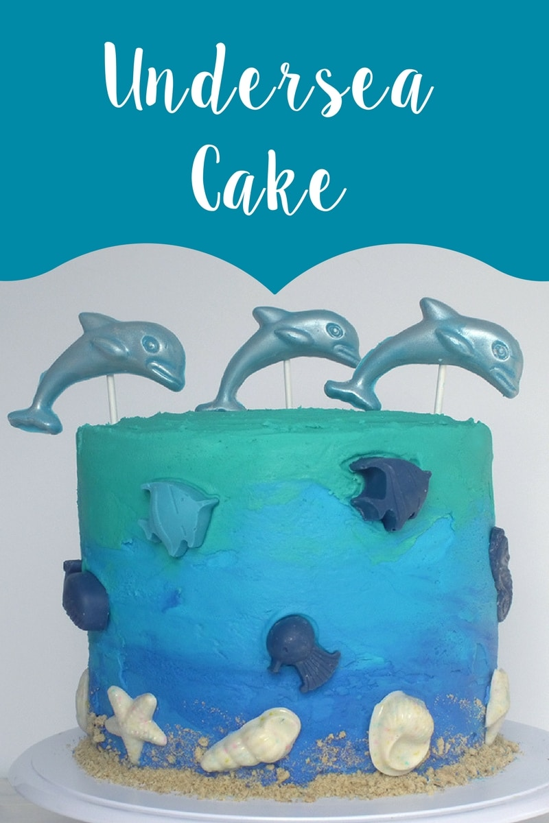 Adorable undersea cake with sea creatures, fish, dolphin, and chocolate seashells. Learn how to recreate this blue ombre cake!