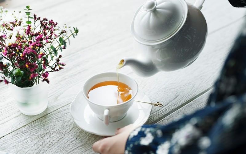 white tea pot with tea cup and hot mother's milk tea