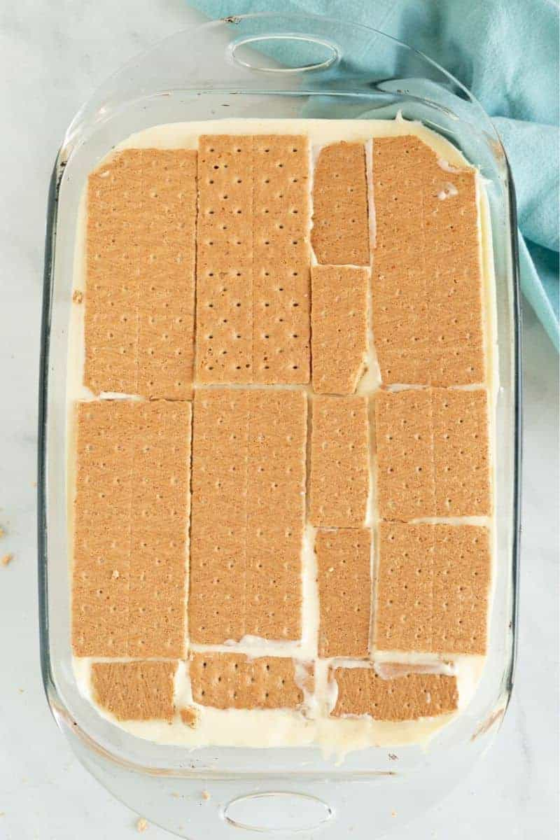 graham crackers layered on French vanilla pudding in an eclair cake