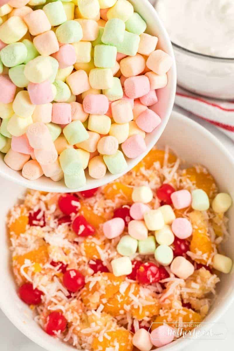 fruit mini-marshmallows being poured into ambrosia salad