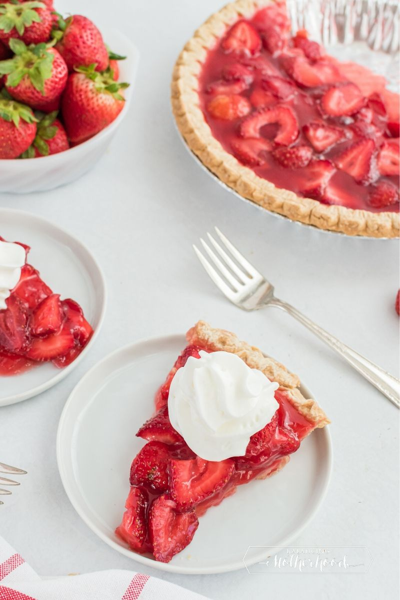 Slice of strawberry pie with whipped cream.