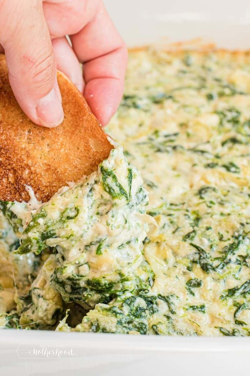 crostini being dipped into hot spinach dip