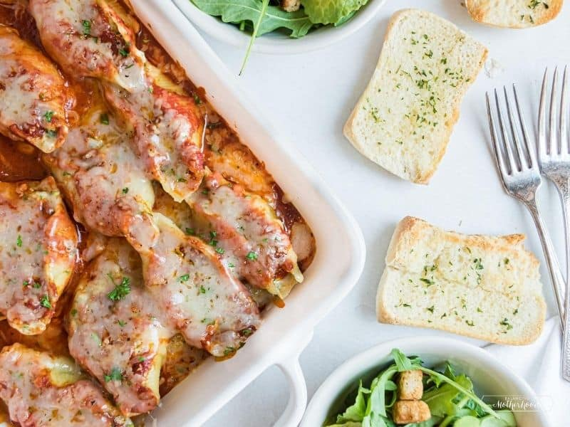Casserole dish with baked stuffed shells and garlic bread on the side.