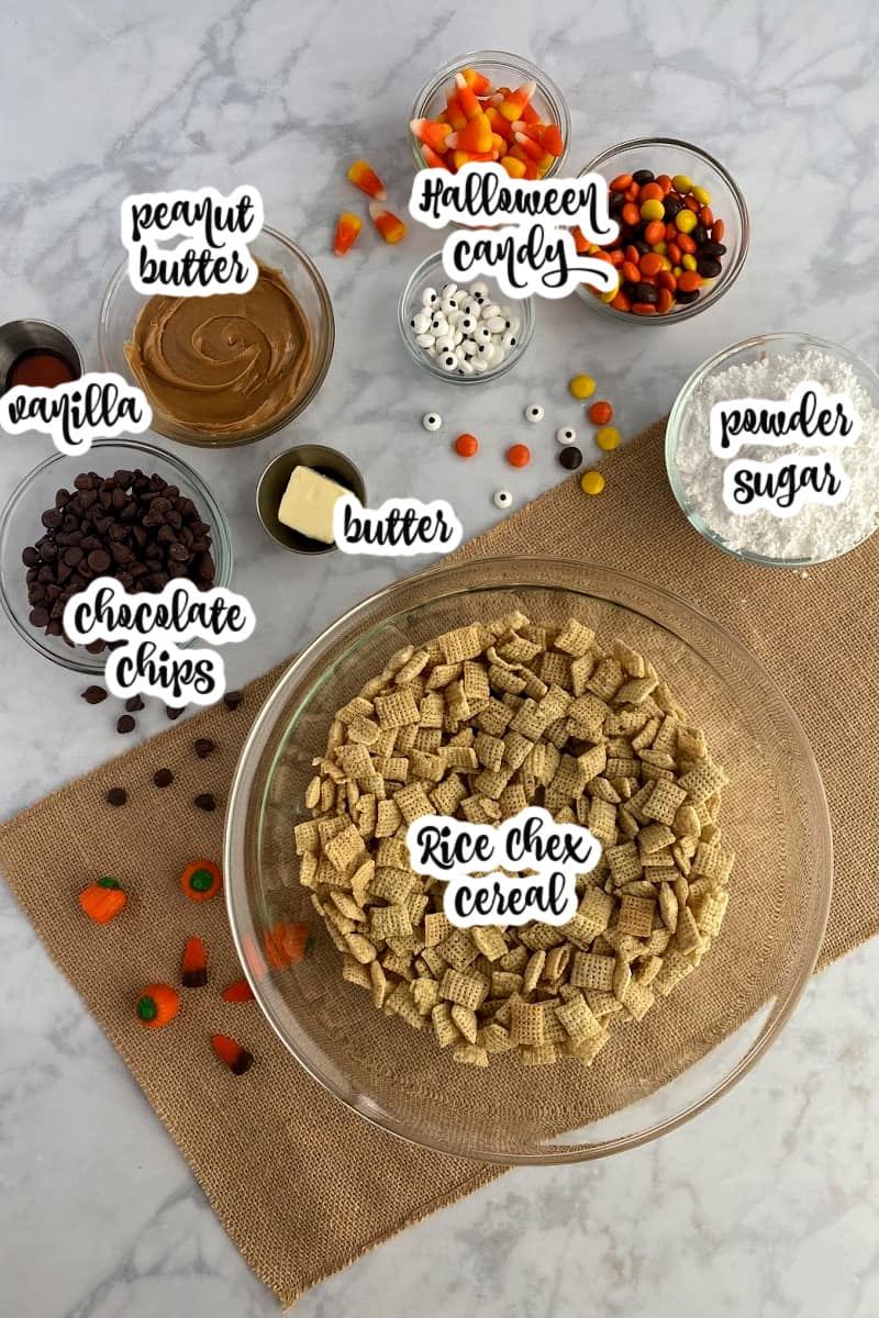 Halloween puppy chow ingredients: Rice chex cereal, chocolate chips, peanut butter, butter, vanilla, powdered sugar, Halloween candy