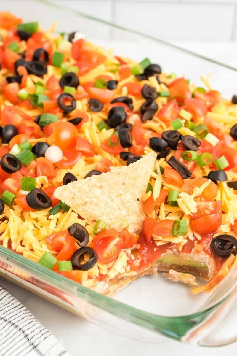 dish with layered dip and a scoop taken out