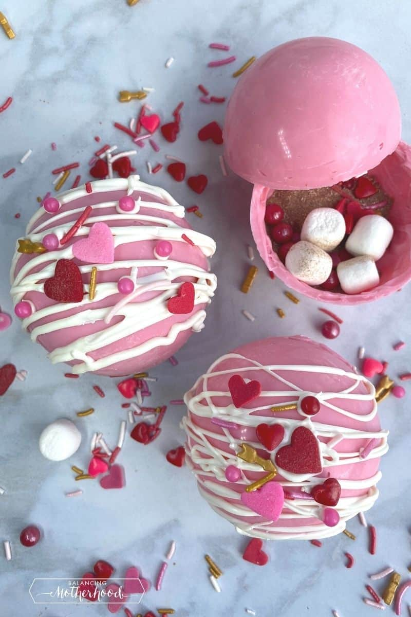 Two pink hot chocolate bombs with heart sprinkles, and one open to show cocoa and mini marshmallows on the inside.