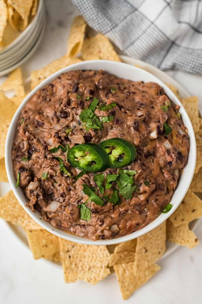 top down of black bean dip with cilantro and jalapenos with chips on the side