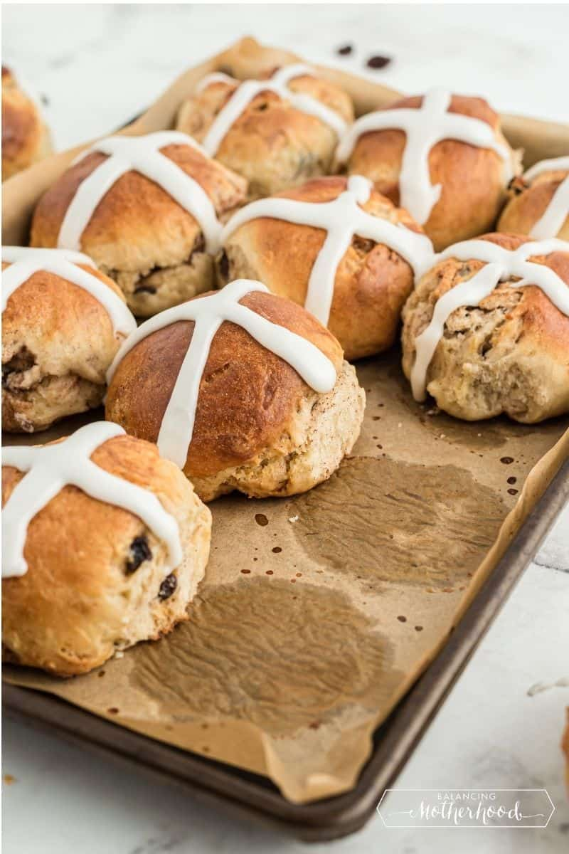 hot cross buns on parchment paper with thick white icing crosses on top