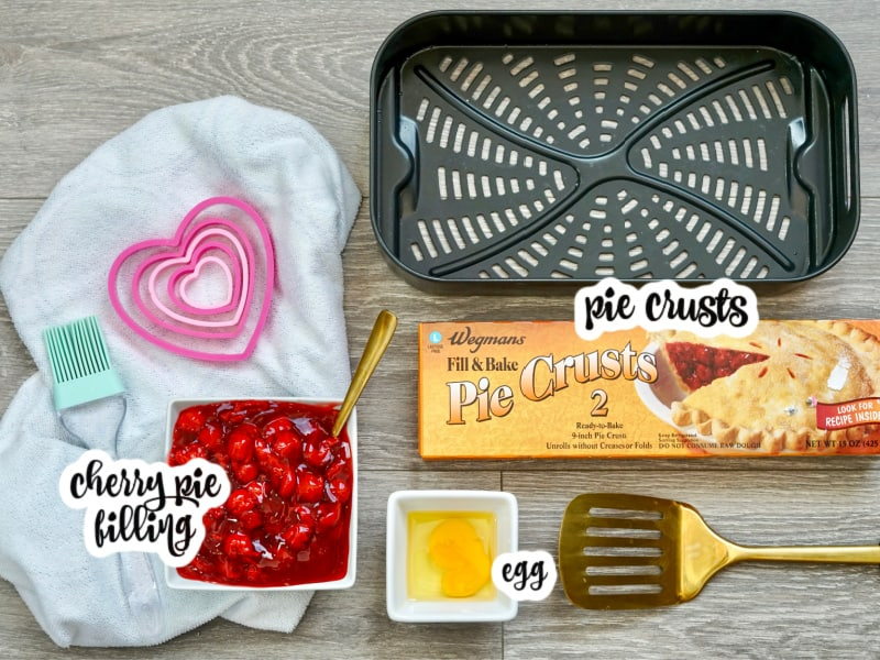 hand pie ingredients: cherry pie filling, egg, packaged pie crusts, shown alongside air fryer