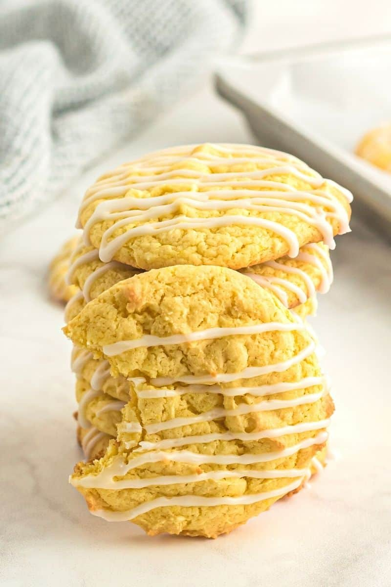 stacked lemon cookies with one cookie on its side with a bite out