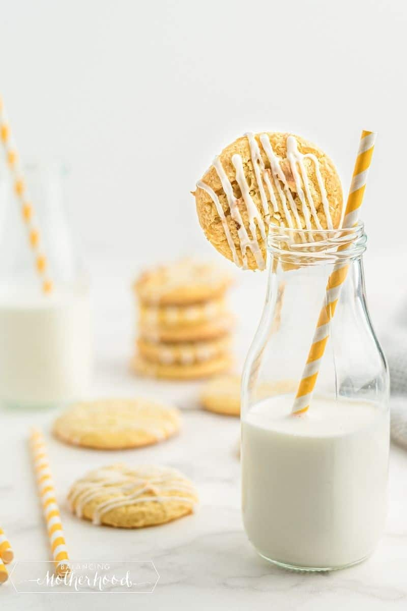 cookie on the edge of a milk glass with yellow and white straw