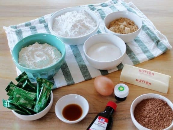 table with ingerdients in bowls: powdered sugar, granulated sugar, brown sugar, butter, cocoa, green food coloring, egg, mint extract, vanilla, Andes mints